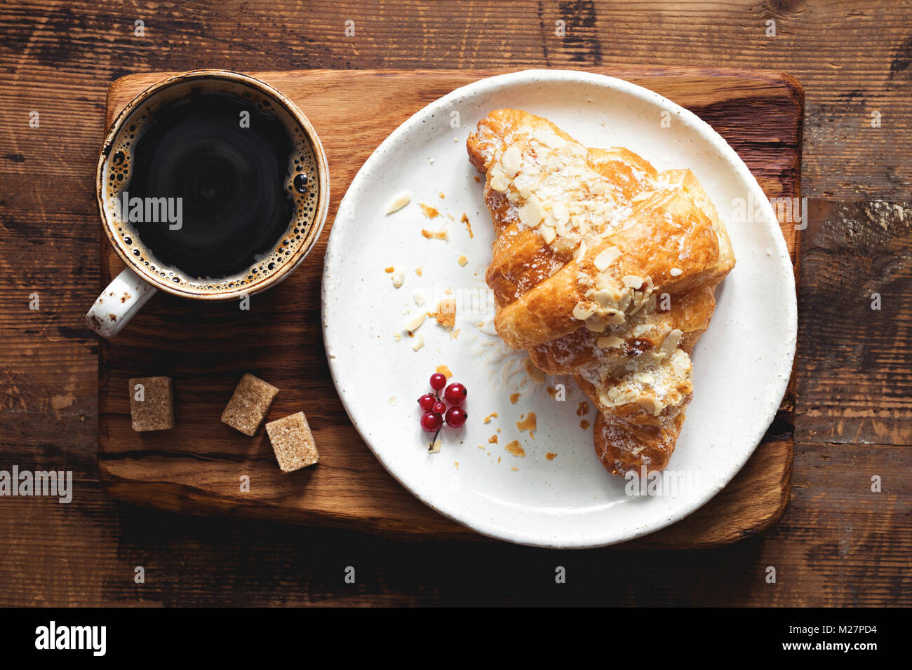 Croissant and cup of coffee espresso on old wooden table. Top view. Breakfast concept - Stock Image
