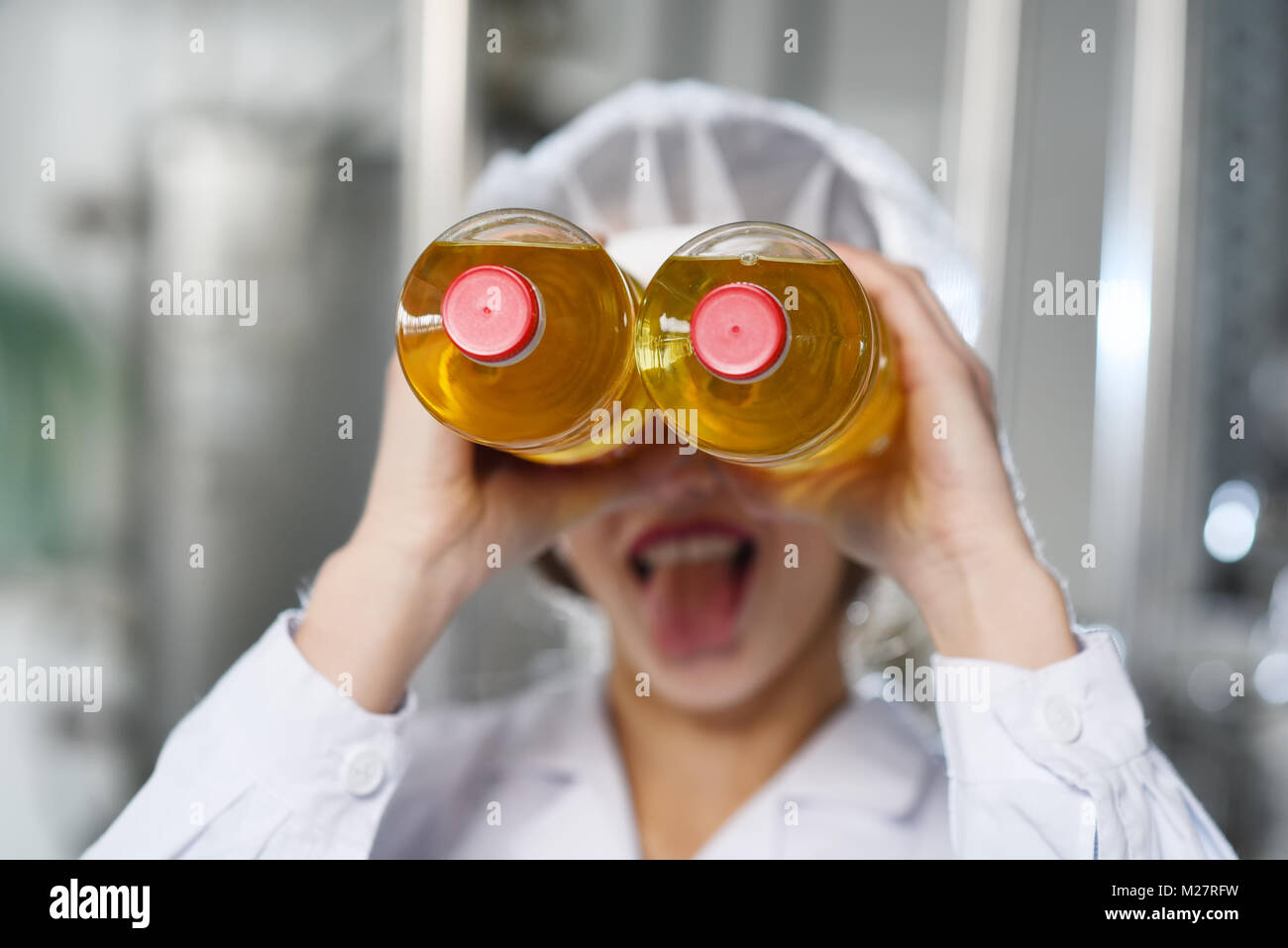 girl sticking out her tongue with bottles - Stock Image
