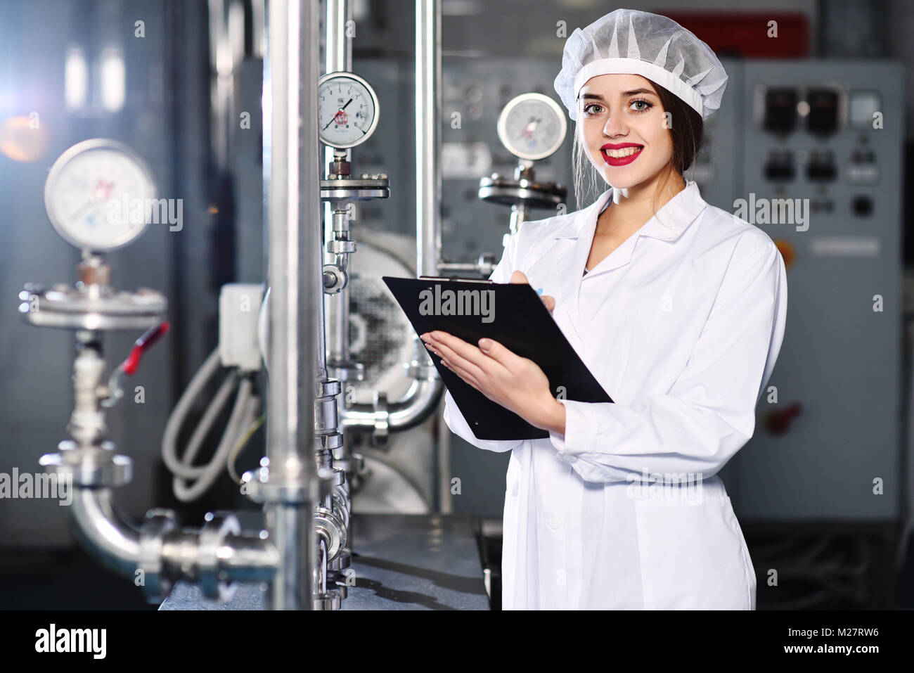 cute girl in white working clothes makes notes on a pen on a tablet on a production background. - Stock Image