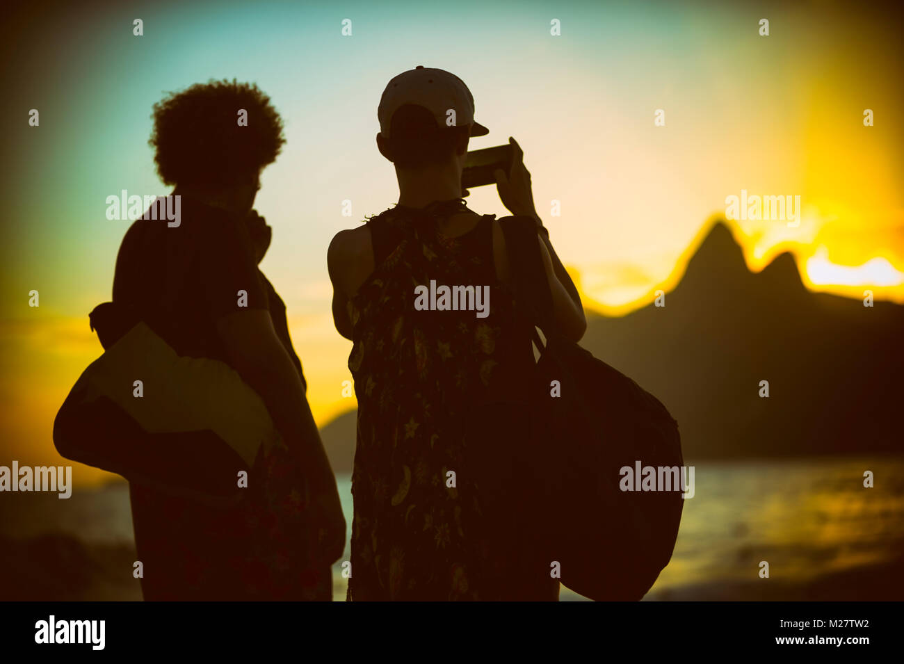 Sunset silhouettes of two unidentifiable tourists taking a photo of two brothers mountains in  Ipanema - Stock Image