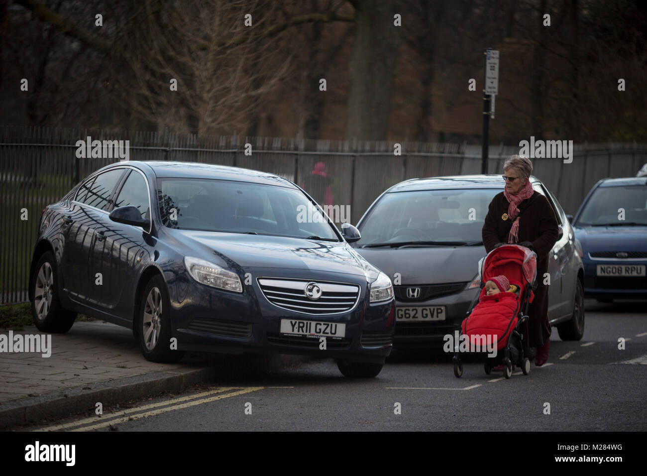 An elderly lady with a child's buggy walks in the road past a mysteriously abandoned Vauxhall car resting at - Stock Image