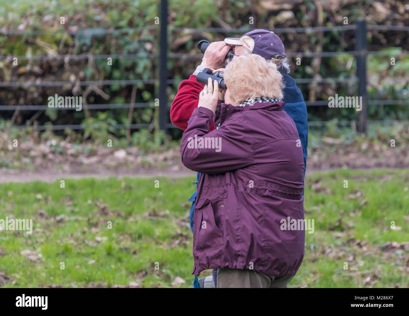 Elderly couple looking through binoculars birdwatching in Winter in England, UK. - Stock Image