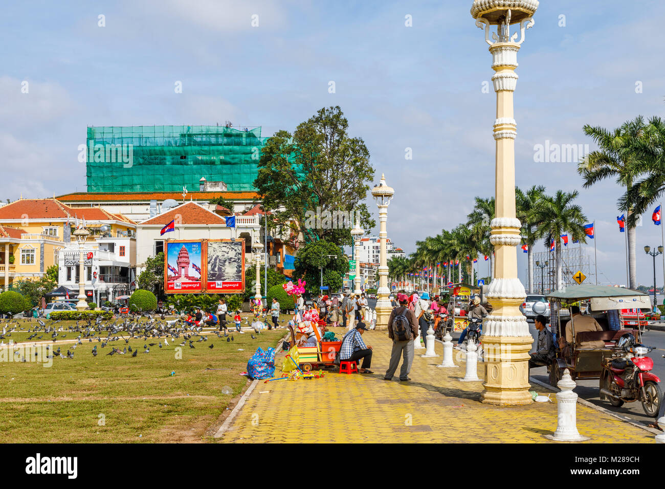 Yellow pavement of the bustling popular waterfront Sisowath Quay promenade by Royal Palace Park, Phnom Penh, capital Stock Photo