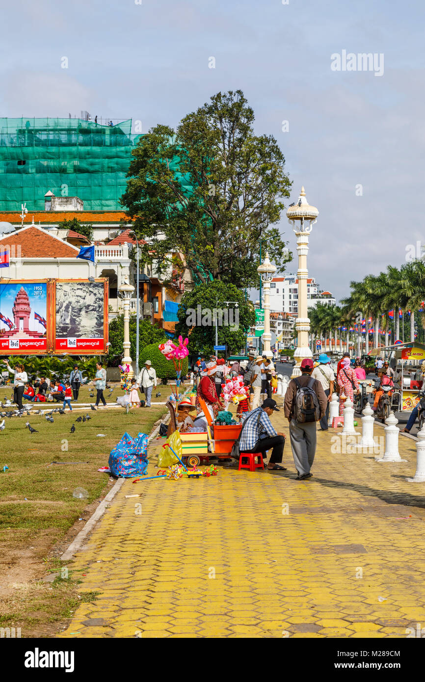 Yellow pavement of the bustling popular waterfront Sisowath Quay promenade by Royal Palace Park, Phnom Penh, capital - Stock Image