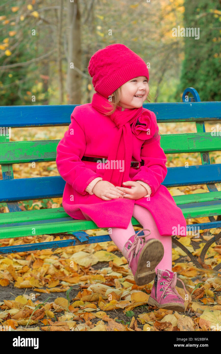 Girl in a pink coat sits on a bench and laughs - Stock Image