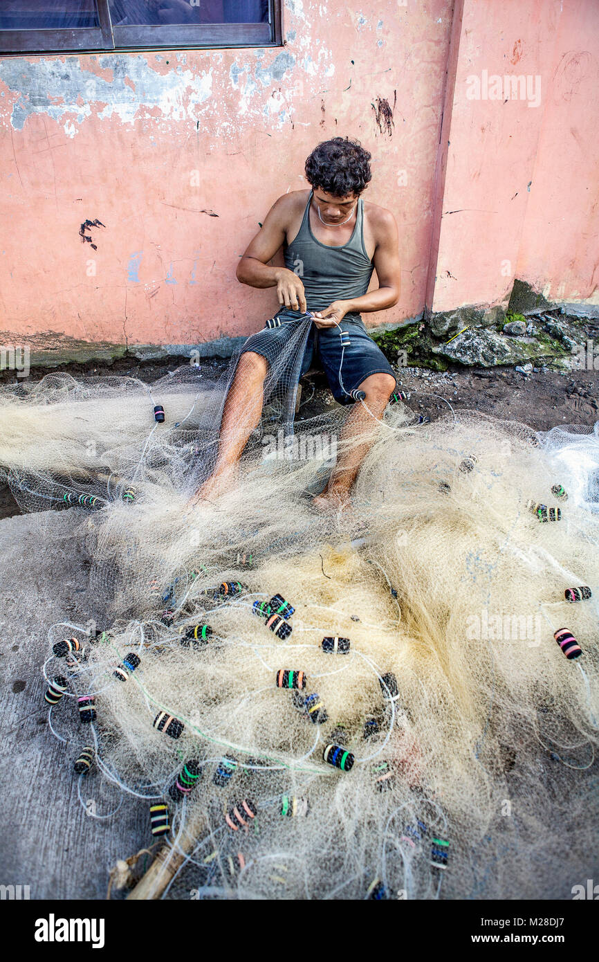 A Filipino fisherman sits mending his seine net, critical equipment for earning his livelihood. - Stock Image