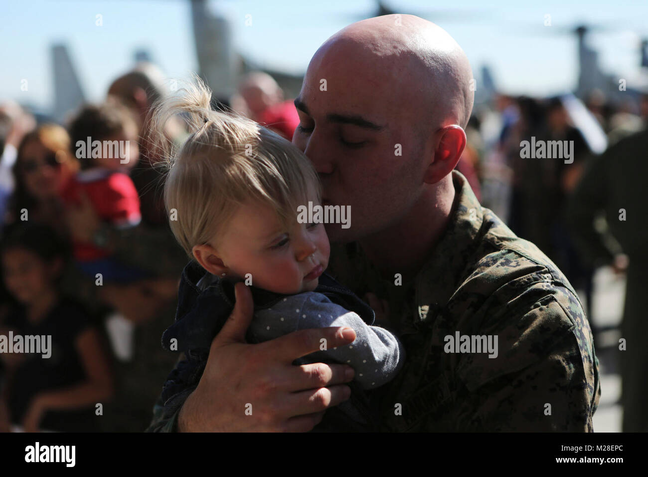 A father reunites with his son following the 15th Marine Expeditionary Unit's aviation combat element's return to Marine Corps Air Station Miramar, Calif., Feb. 1. During the deployment, more than 4,500 Marines and Sailors of the America Amphibious Readiness Group and embarked 15th MEU conducted maritime security operations and multiple military-to-military exchanges with partner nations in support of regional security, stability and the free flow of maritime commerce in the Indo-Asia-Pacific and Middle East regions. Stock Photo
