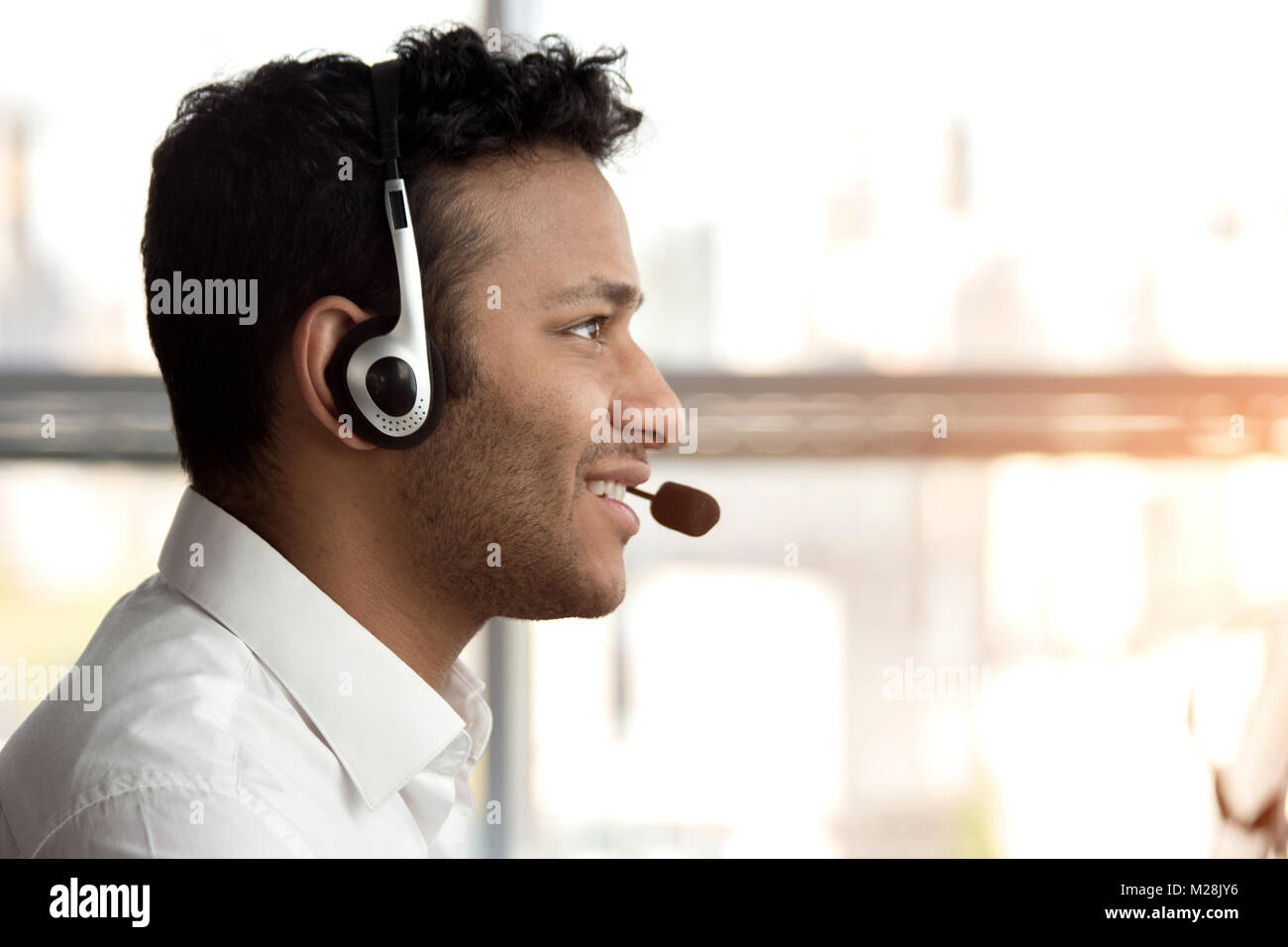 Side view stubbled black man with headset. Smiling black indian man with headset, close up. - Stock Image