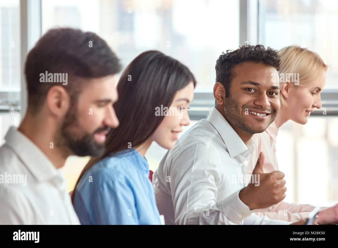 Sitting young indian black man showing thumb up. Young adult stubbled black man showing approval gesture, thumb - Stock Image