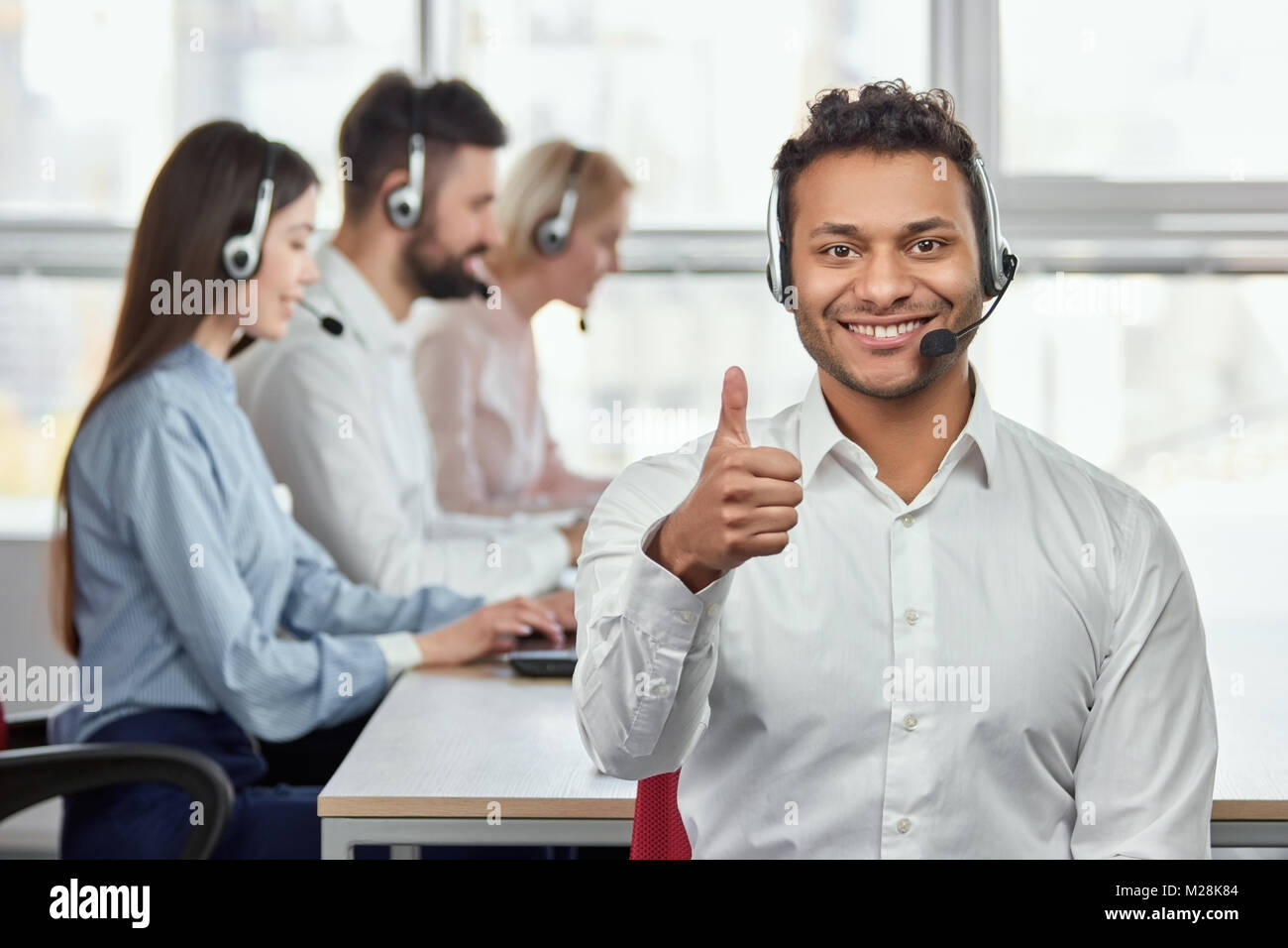 Cheerful american black operator with thumb up. Portrait of young male customer service representative, working - Stock Image