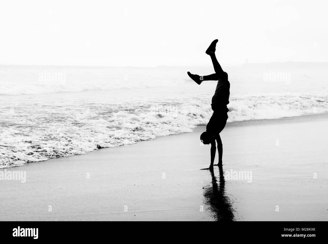 Headstand on a beach in Ghana - Stock Image