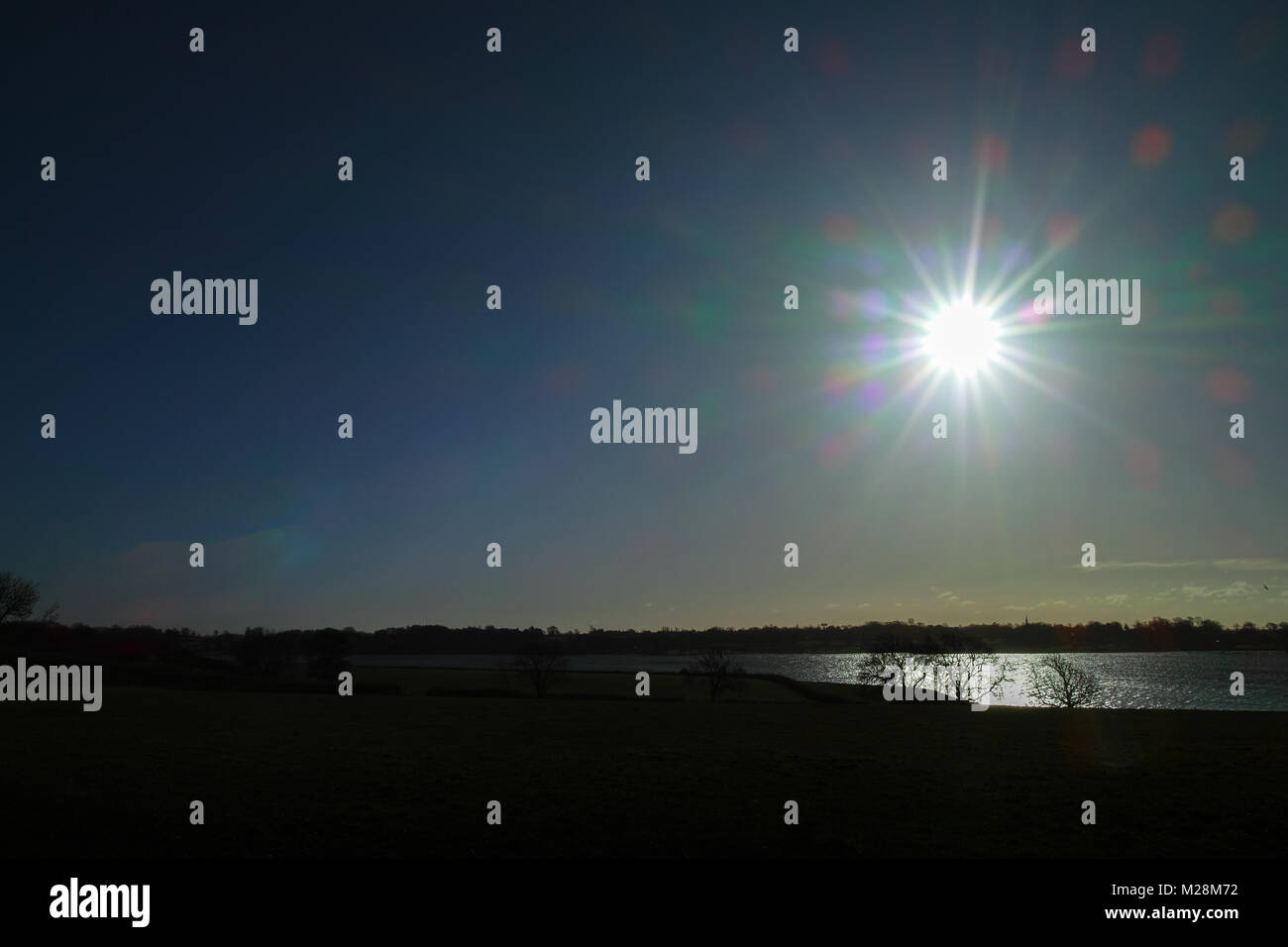 Starburst over a lake - Stock Image