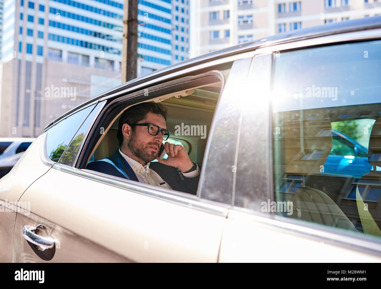 Young businessman sitting in the backseat of a car talking on a cellphone while being driven through the city - Stock Image