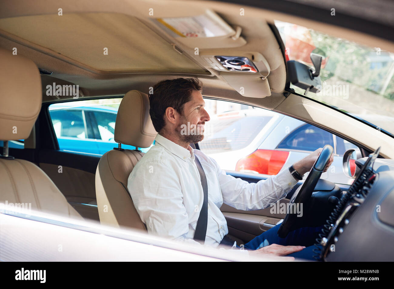 Smiling young man sitting in his car driving through the city during his morning commute - Stock Image