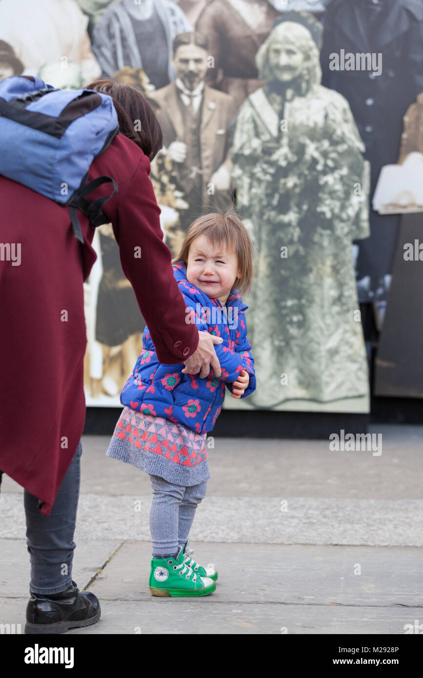 Trafalgar Square, London, 6th Feb 2018. A little girl is not yet fully convinced of the suffragette's movement. - Stock Image