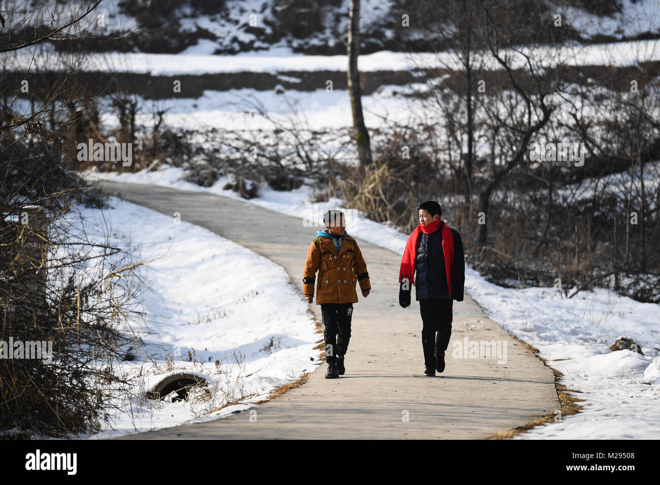 (180206) -- KANGLE, Feb. 6, 2018 (Xinhua) -- Sun Jianjun (R) and his younger brother Sun Jianqiang walk in Xinzhuang - Stock Image