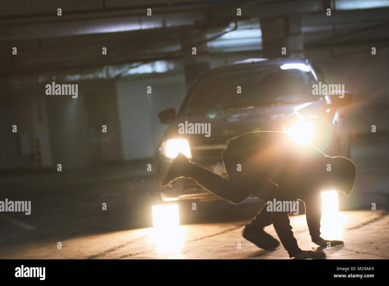 Man acrobat shows tricks somersault at underground parking - Stock Image