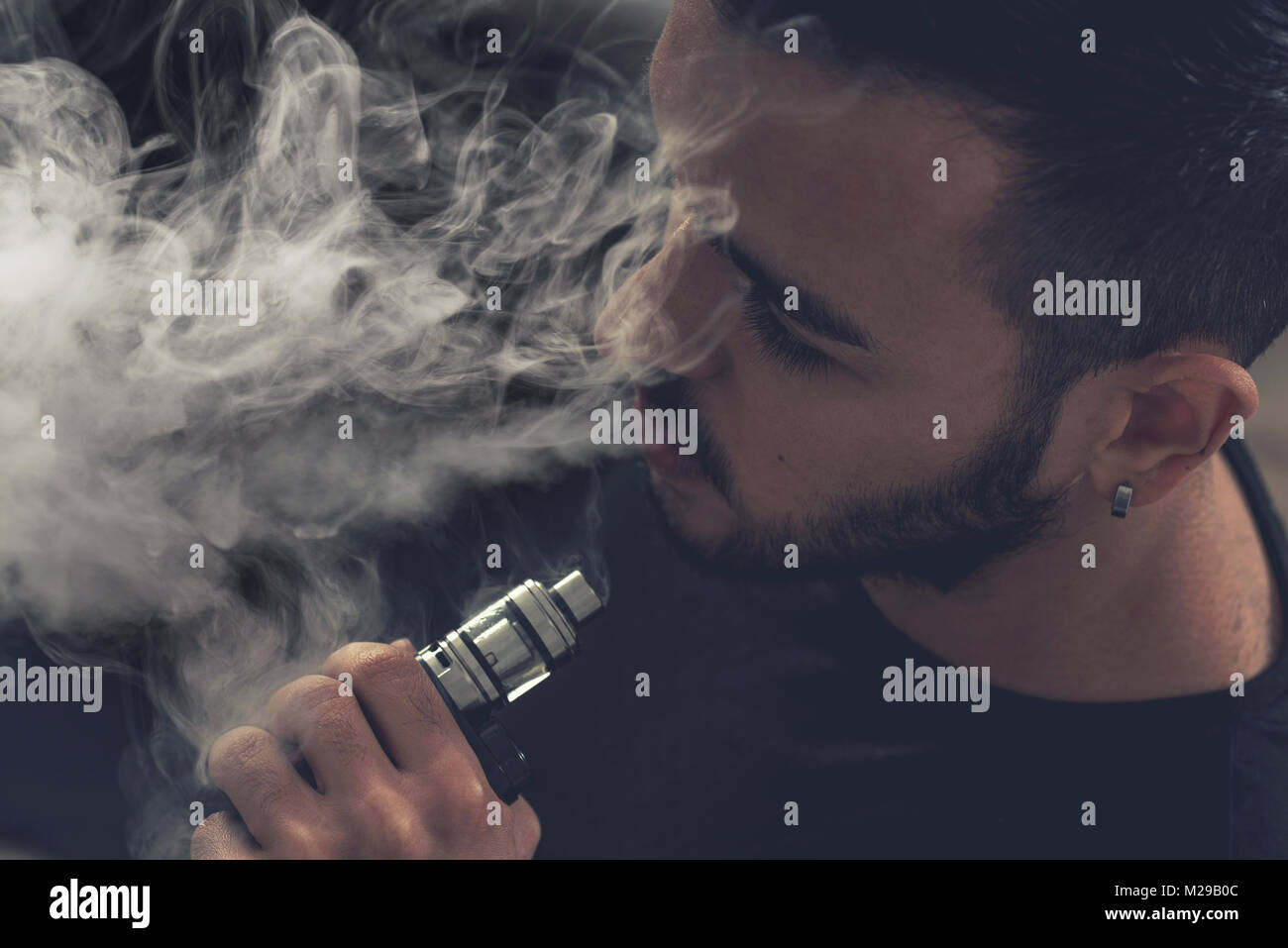 Hand holding an electronic cigarette over a dark background - Stock Image