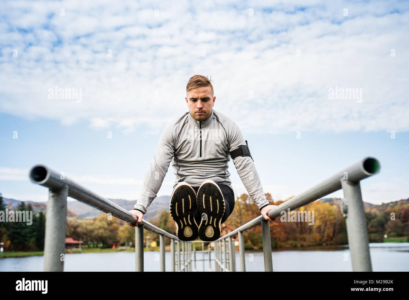 Young man doing exercise in park. - Stock Image