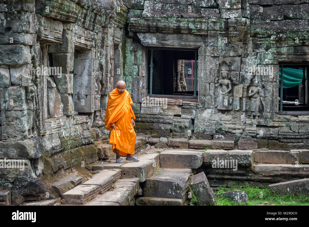 Monk in orange robe in an ancient temple in Angkor Wat, Siem Rep, Cambodia - Stock Image
