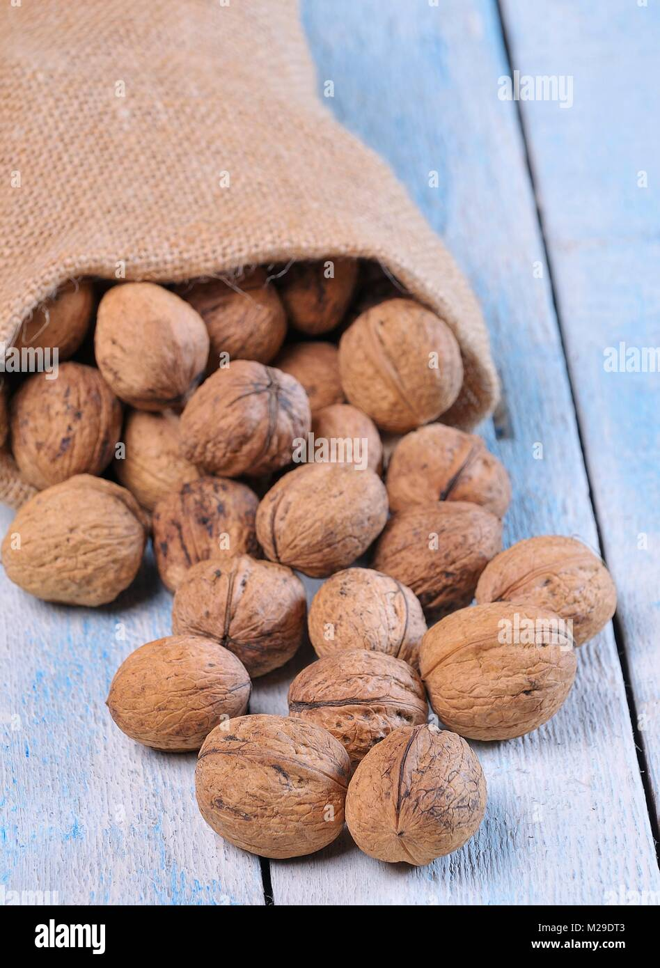 Walnuts on wooden table in the kitchen. - Stock Image