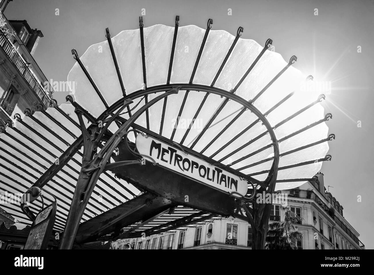 Metropolitain art nouveau sign with a glass roof in paris france black and white