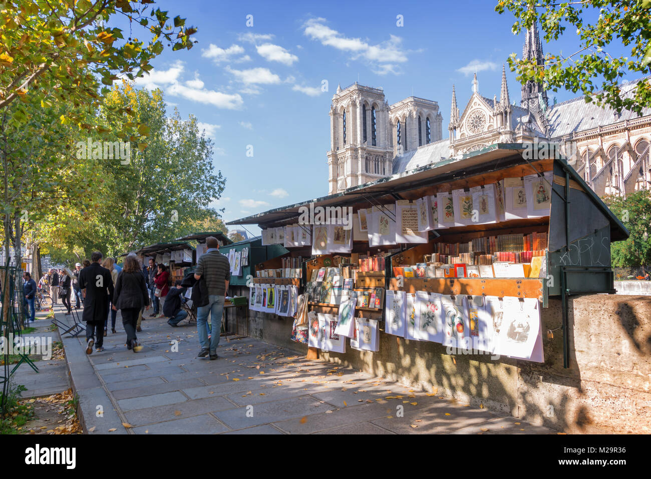 Tourists walking by the famous bookseller's boxes (bouquinistes) along the Seine River near Notre Dame in Paris, - Stock Image