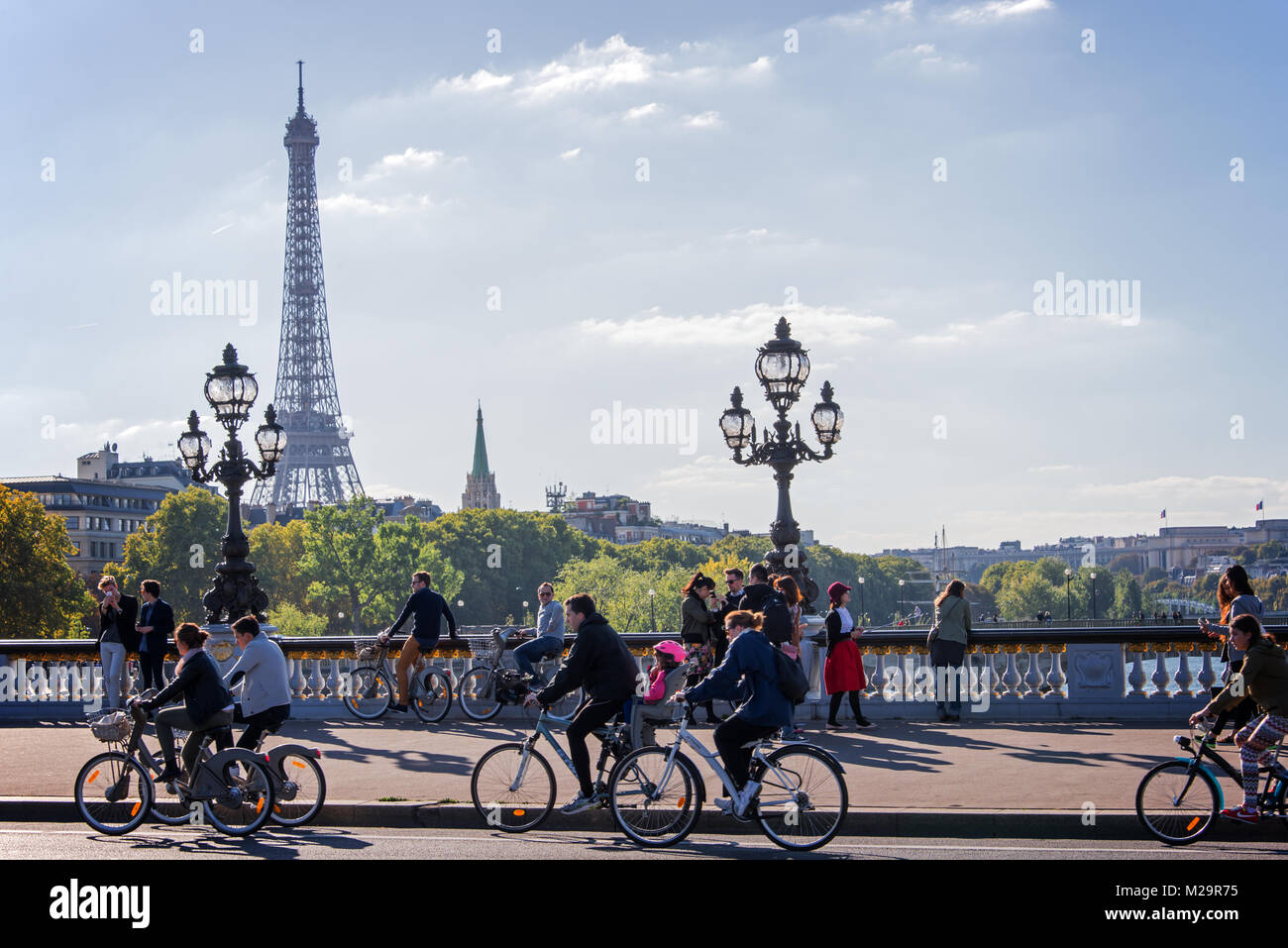 People on bicycles and pedestrians enjoying a car free day on Alexandre III bridge in Paris, France - Stock Image