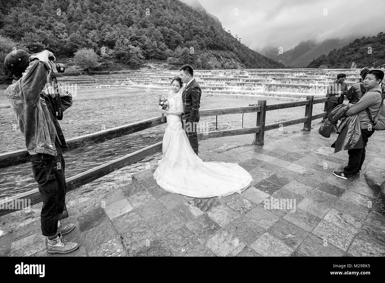 Lijiang, China - September 22, 2017: Wedding couple photo shoot at the White Water River in Blue Moon Valley, one - Stock Image