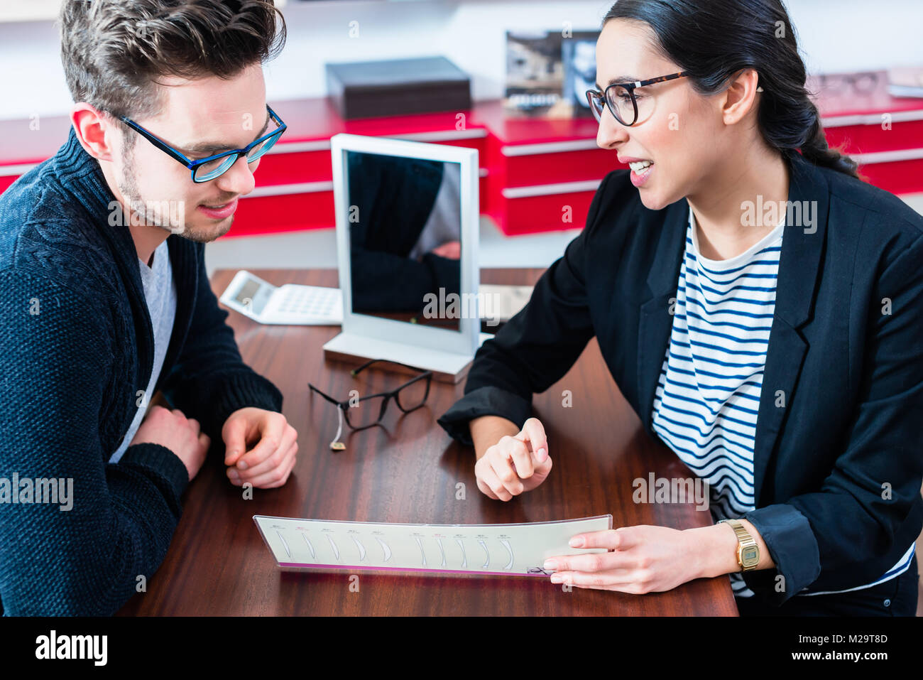 cb5443ddee Man at optician shop getting advice from sales woman Stock Photo ...