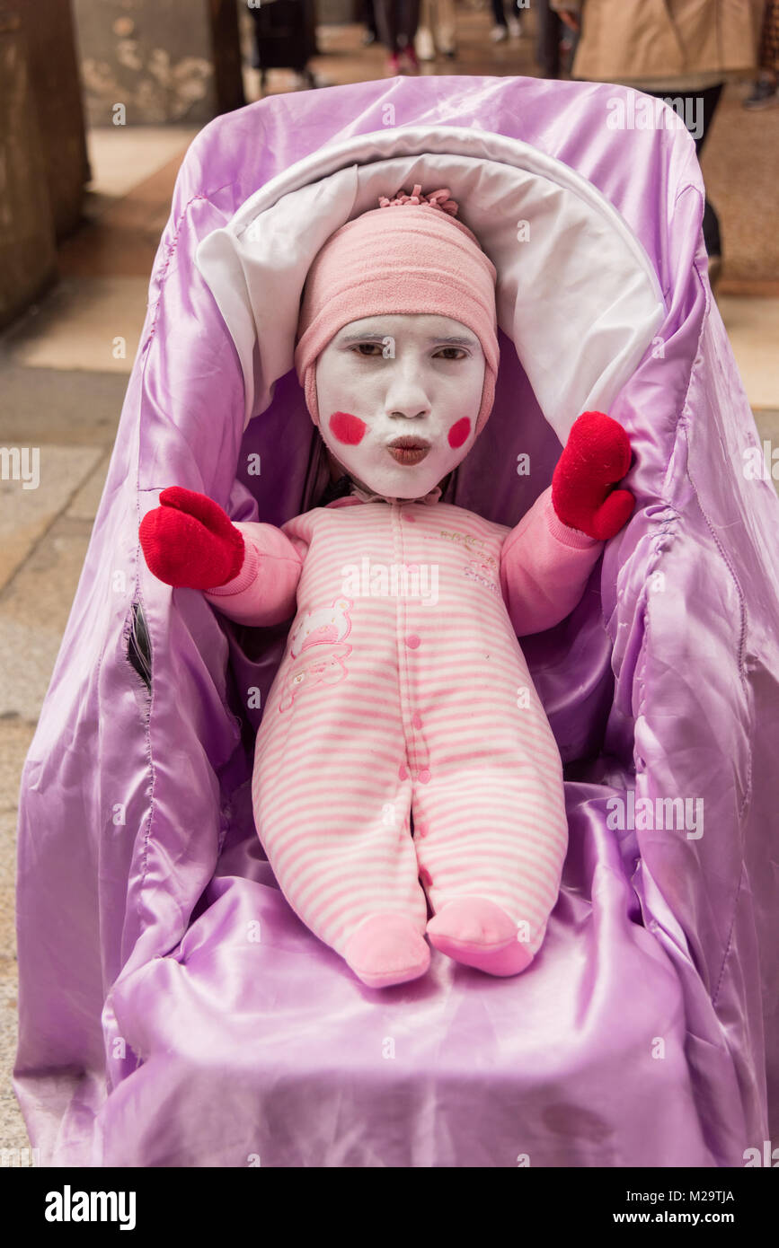 A street performer or busker dressed as a baby in a pram in Bologna Italy - Stock Image