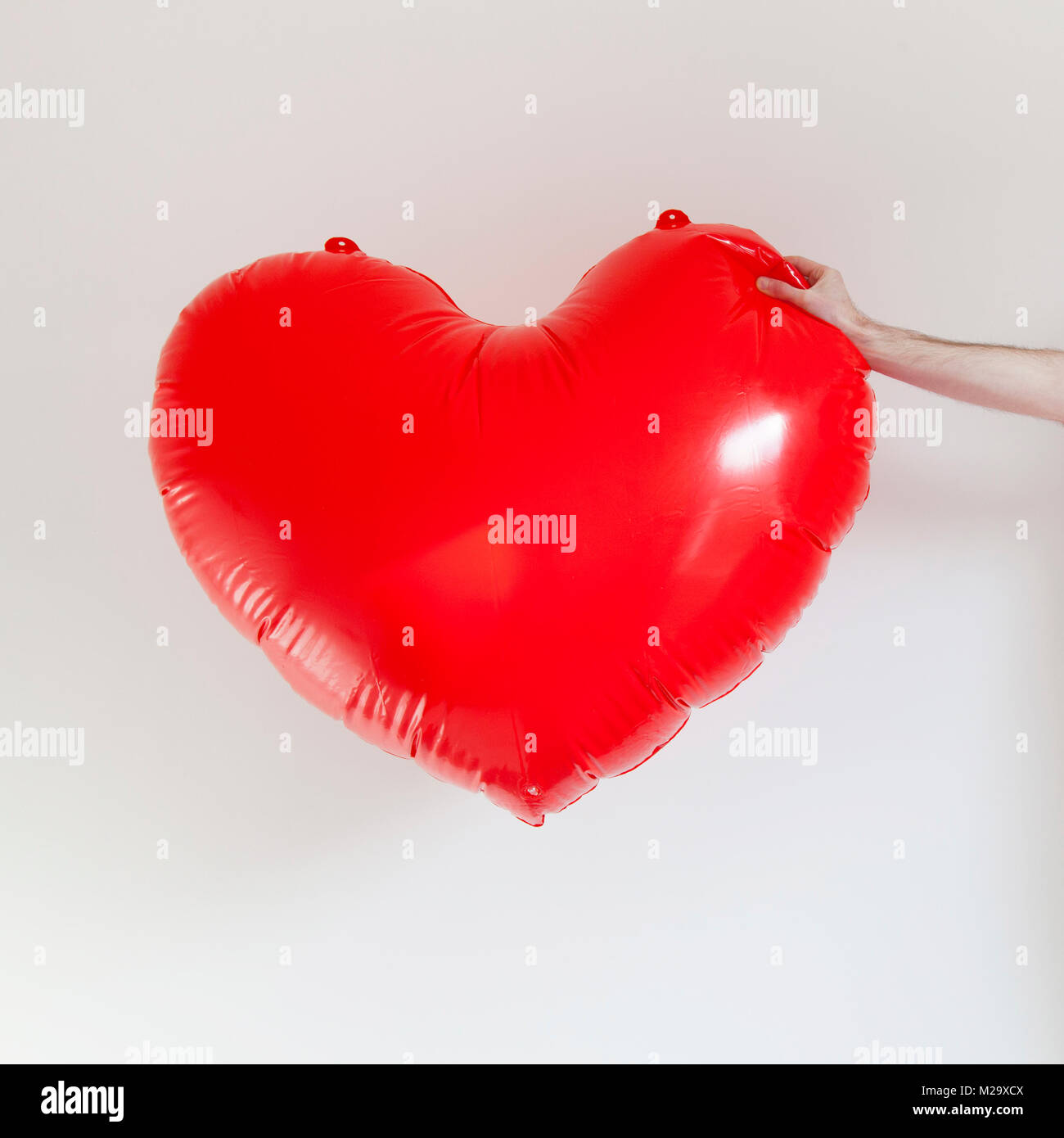 Hands Holding A Large Inflatable Heart Shape