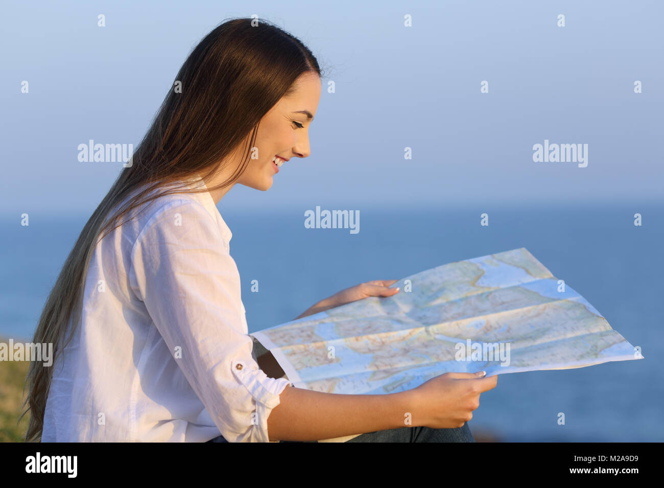 Profile of a happy tourist sitting on the grass consulting a guide map on the beach - Stock Image