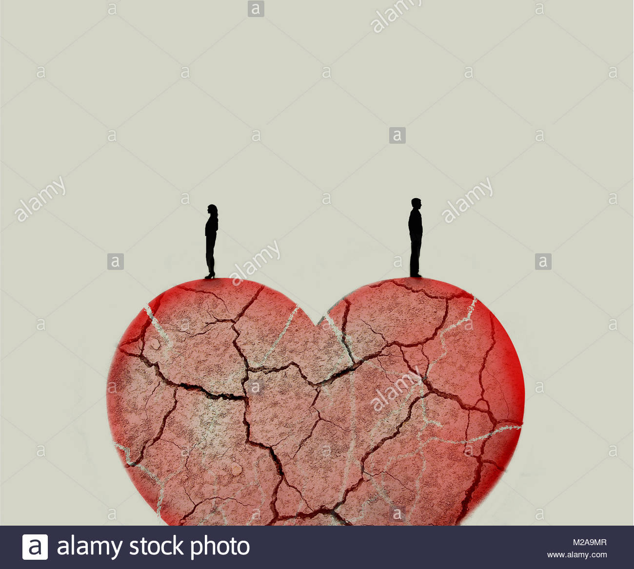 Couple standing on top of broken heart - Stock Image