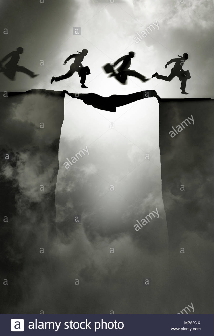 Man making a bridge for colleagues to cross gap - Stock Image