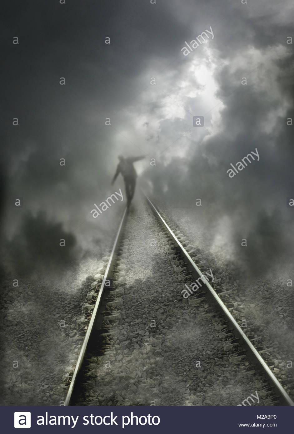 Businessman balancing on railway line - Stock Image