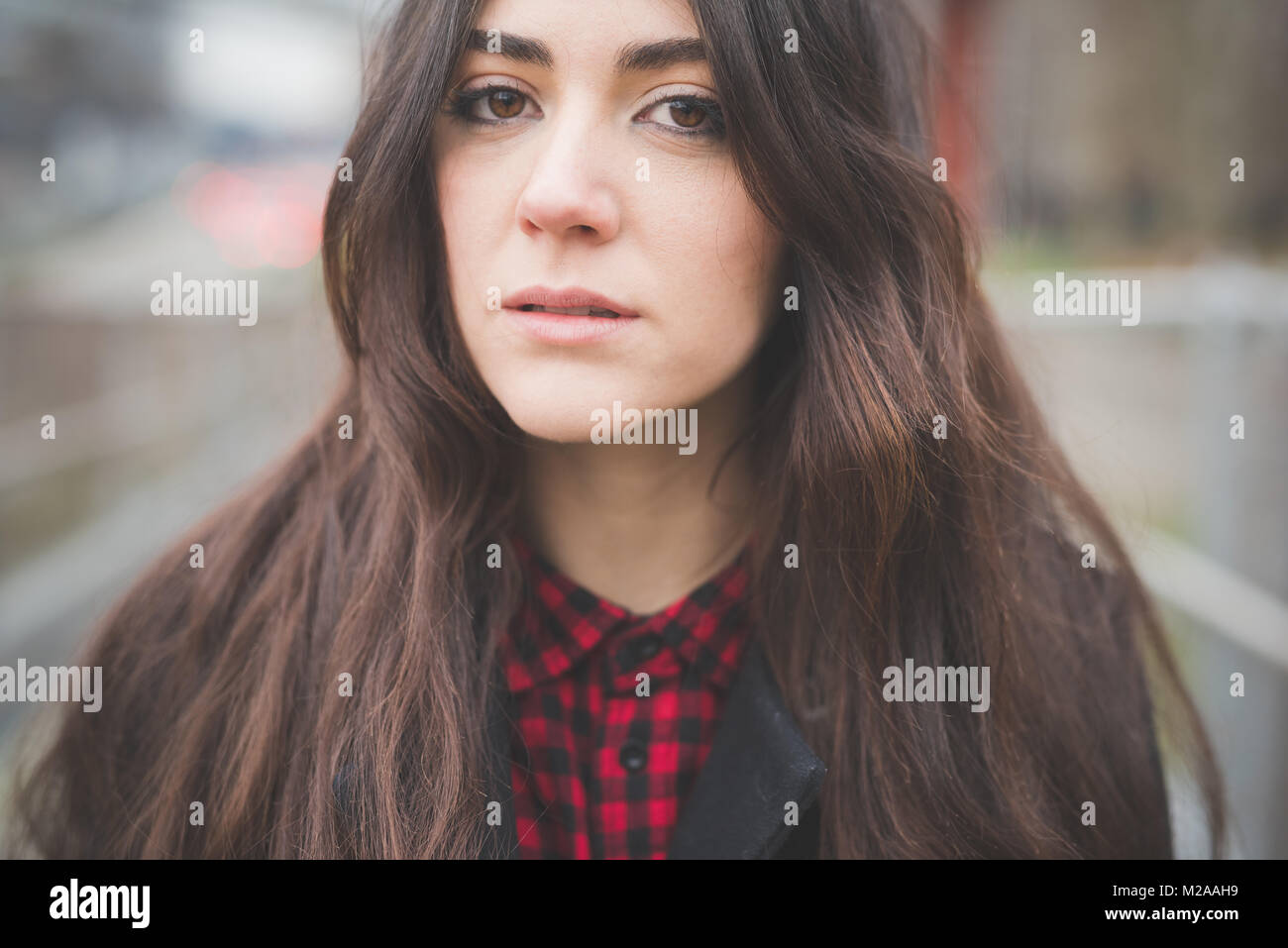 portrait young woman outdoor looking camera melancholic - assertiveness, carefree, freshness concept - Stock Image