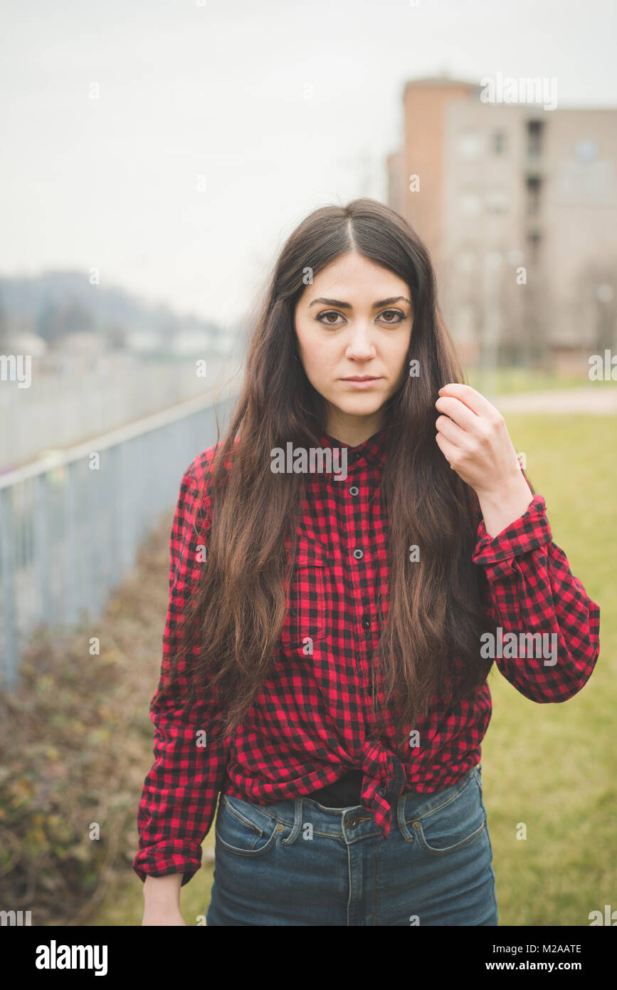 young beautiful woman posing outdoor looking camera angry - anger, assertiveness, serious concept - Stock Image
