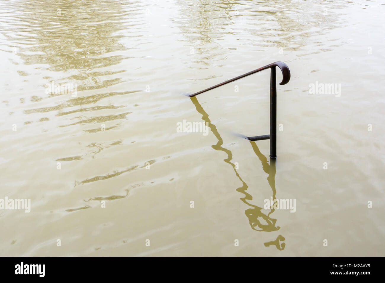 The upper part of a wrought iron handrail is sticking out of the muddy floodwaters of the swollen Seine during a - Stock Image