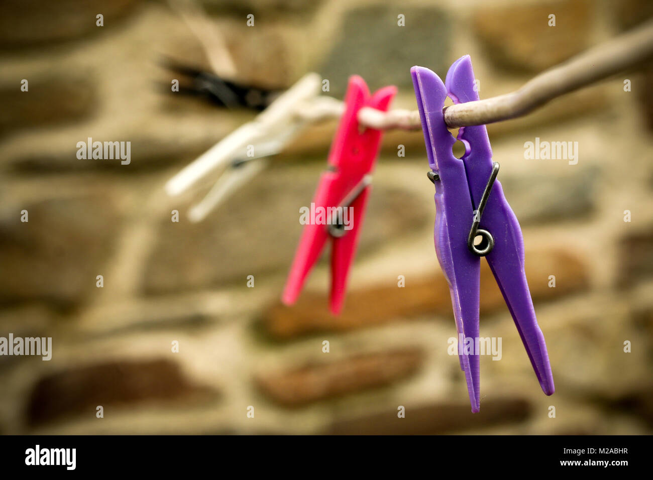 A detail of colorful clothes pegs on a line. - Stock Image