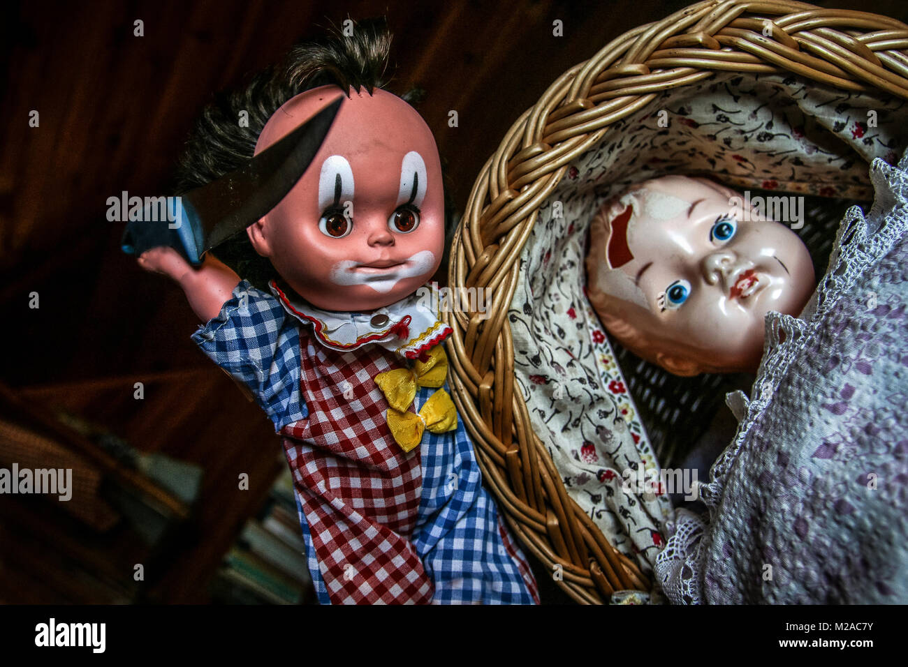 The unused old doll with a hole in its head is lying in the baby carriage and looking quite scary and depressive. - Stock Image