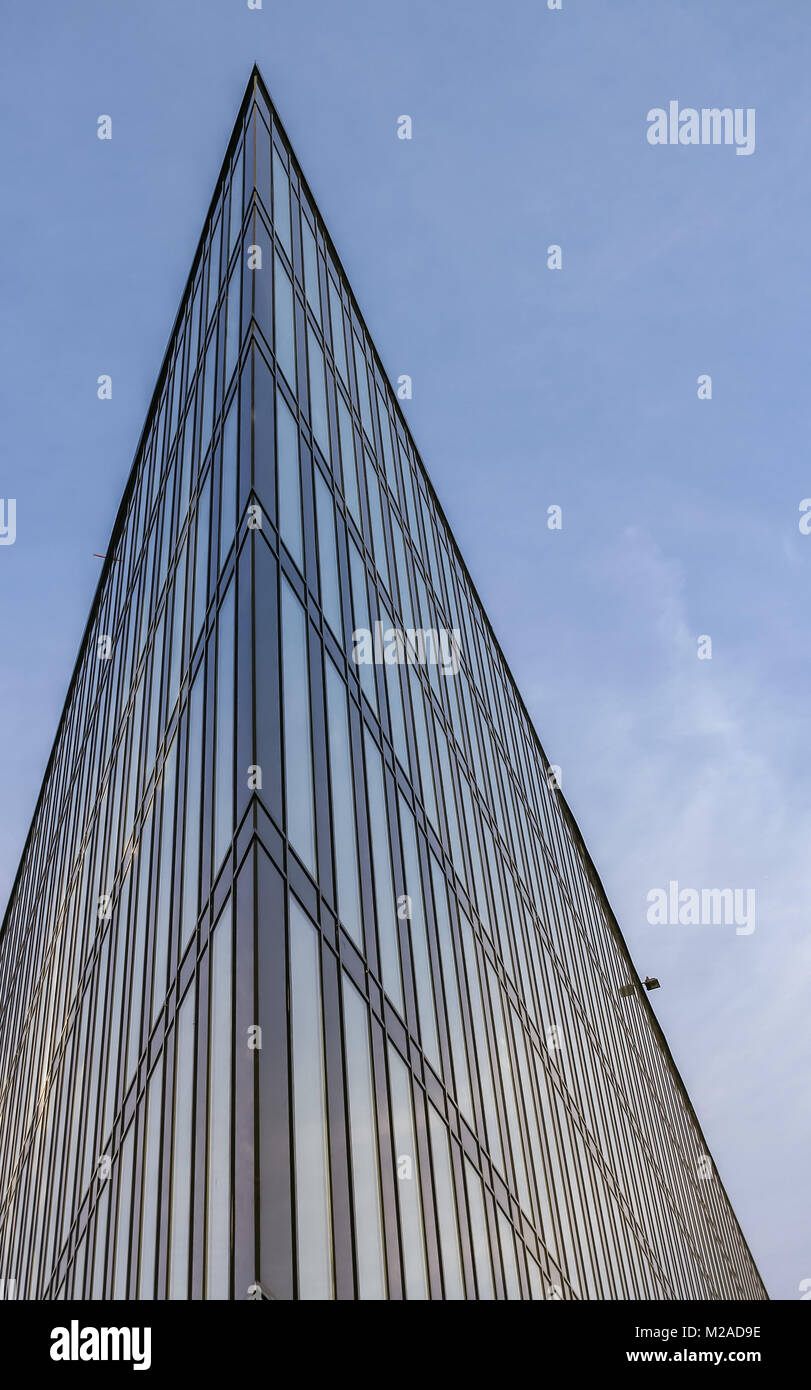 An acute part of a modern building directed upward to the blue sky. - Stock Image