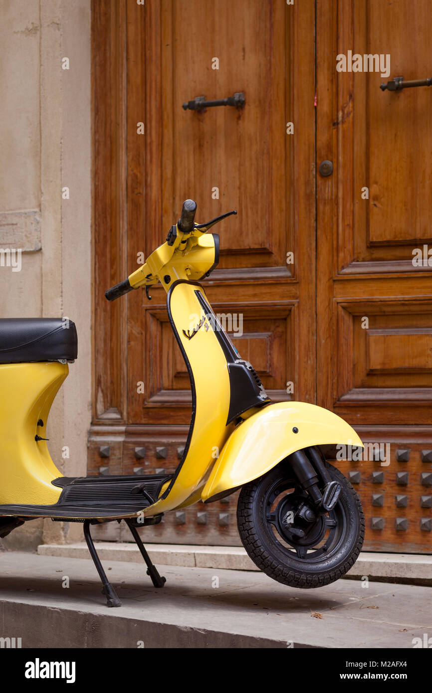 Just enough parking space for this tiny yellow motor scooter at the front door, Montalcino, Tuscany, Italy - Stock Image