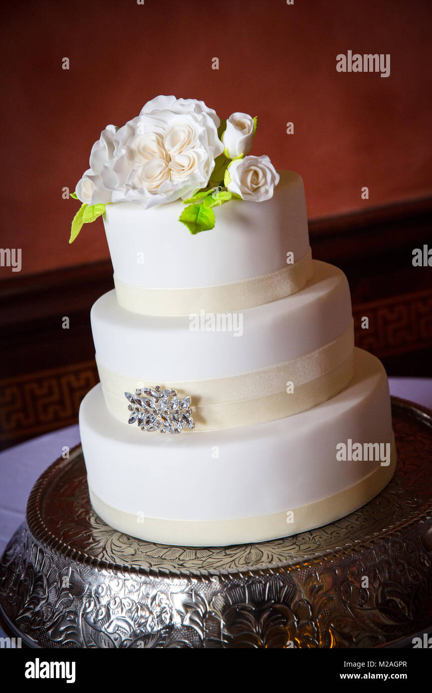 Three tiered white icing wedding cake with iced flower decoration - Stock Image