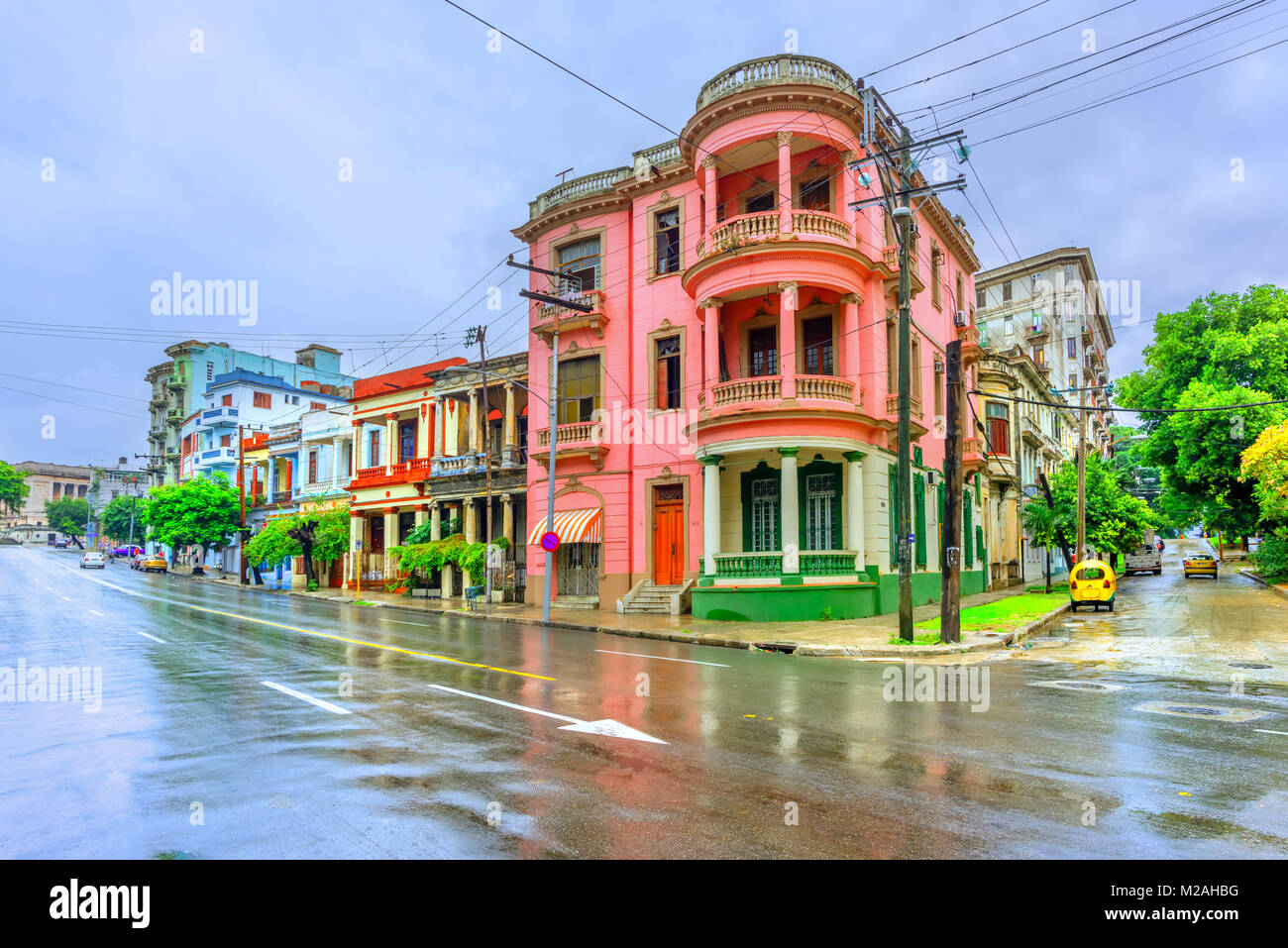 Ancient multi-colored buildings with columns on the street of Cuban Havana at noon after rain, asphalt and blue - Stock Image