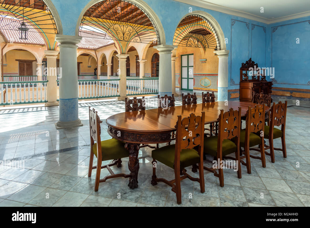 Blue hall with columns, brown, wooden table and carved chairs, marble floor and a view of the tiled roof in the - Stock Image