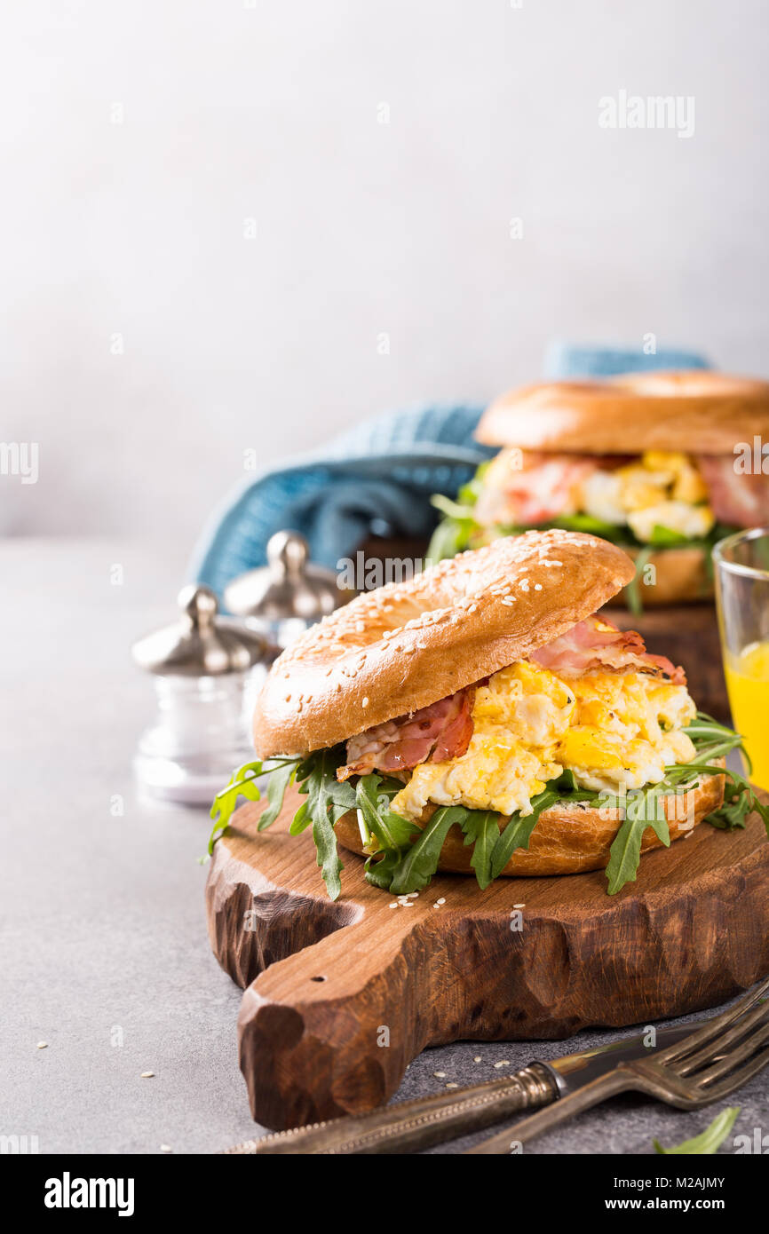 Freshly baked bagel filled with scrambled eggs - Stock Image
