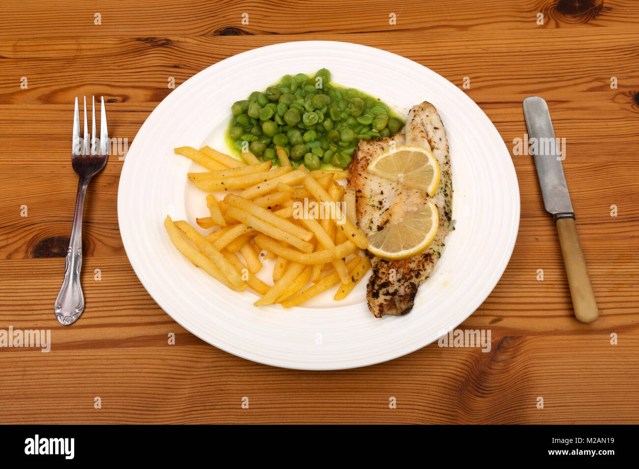 Sea Bass with chips and processed peas - Stock Image