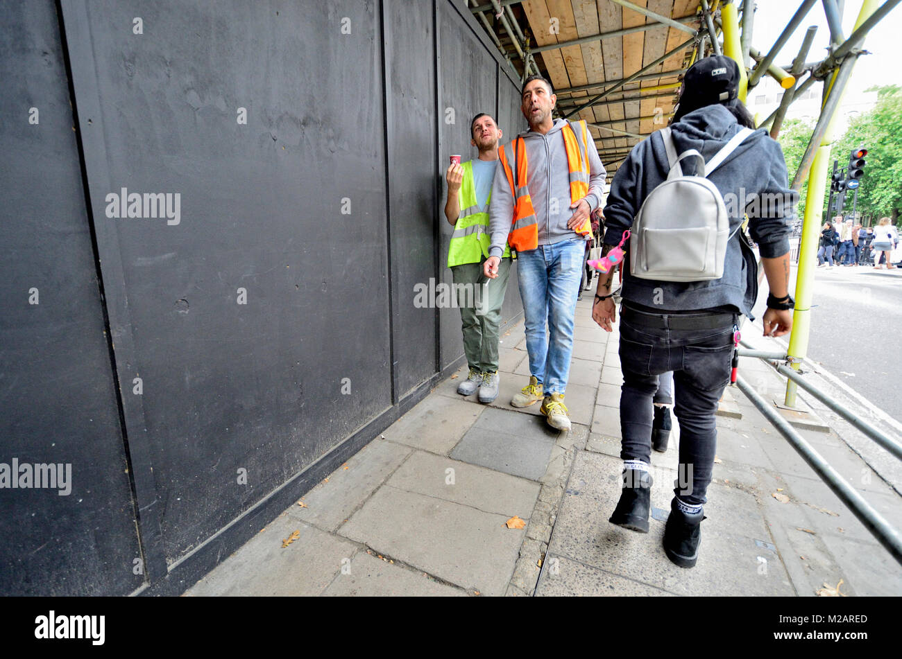 London, England, UK. Workmen in hi-vis jackets walking under scaffolding, one with a cigarette, one with coffee - Stock Image