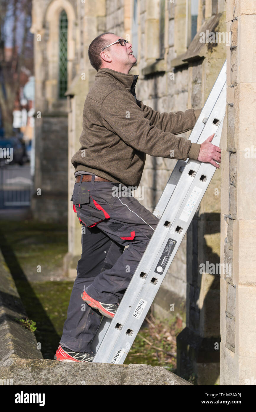 Workman climbing up a ladder. - Stock Image